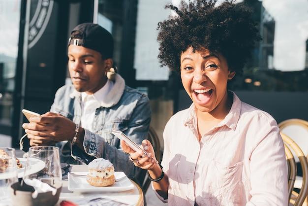 Schwarzes junges paar mit smartphones