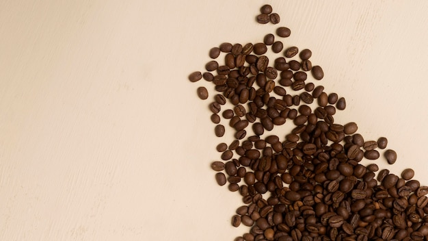 Schwarzes kaffeebohnensortiment auf beigem hintergrund mit kopienraum