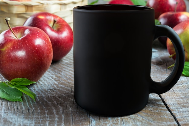 Schwarzes kaffeetassemodell mit äpfeln