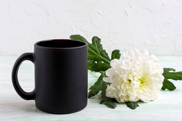 Schwarzes kaffeetassenmodell mit sanfter weißer chrysantheme