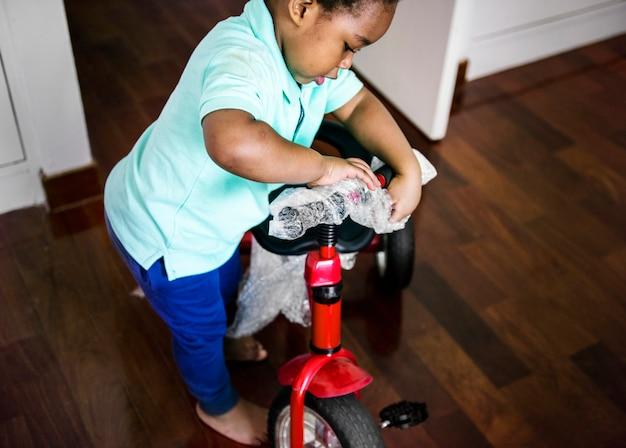 Schwarzes kind, das fahrrad auspackt