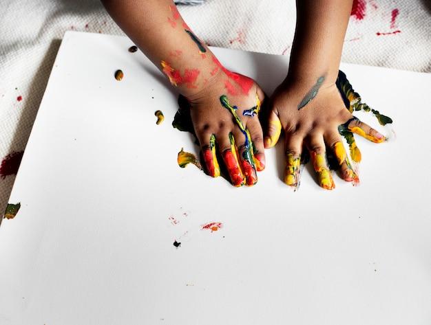 Schwarzes kind, das seine malerei genießt