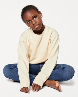 Schwarzes kind im cremefarbenen pullover