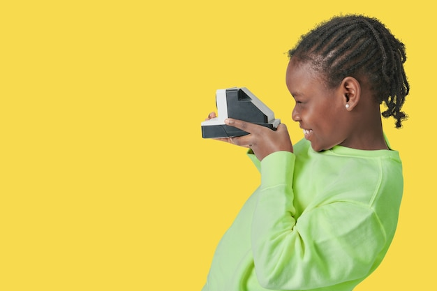 Schwarzes kind mit sofortbildkamera