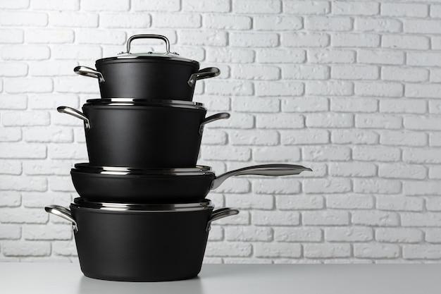 Schwarzes küchengeschirr auf tisch gegen weiße backsteinmauer, vorderansicht
