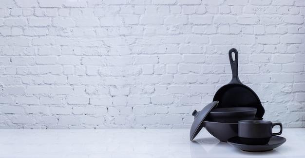Schwarzes küchengeschirr auf weißer backsteinmauerbeschaffenheit