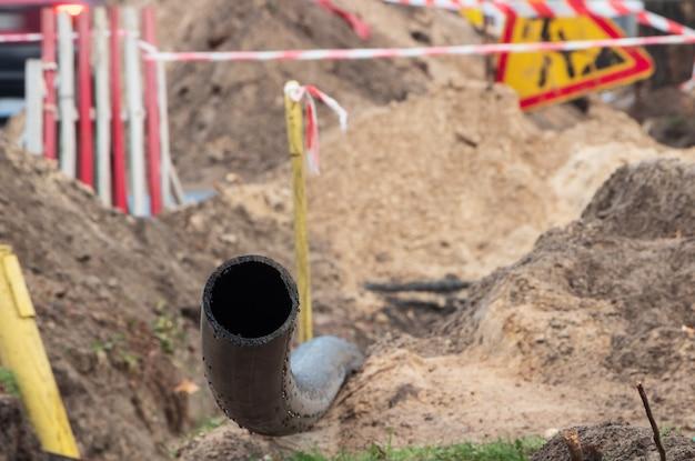 Schwarzes kunststoffrohr zur unterirdischen wasserversorgung. pvc rohr. reparatur des abwassersystems. nahansicht.