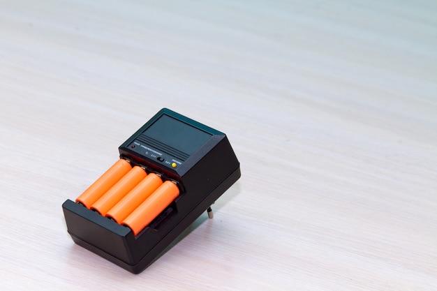 Schwarzes ladegerät mit orangefarbener aaa-batterie