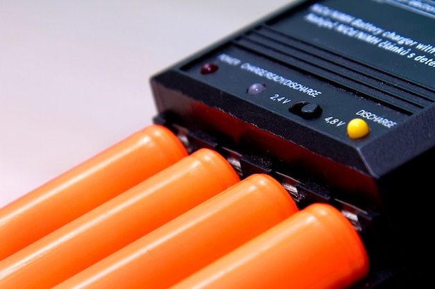 Schwarzes ladegerät mit orangefarbener batterie