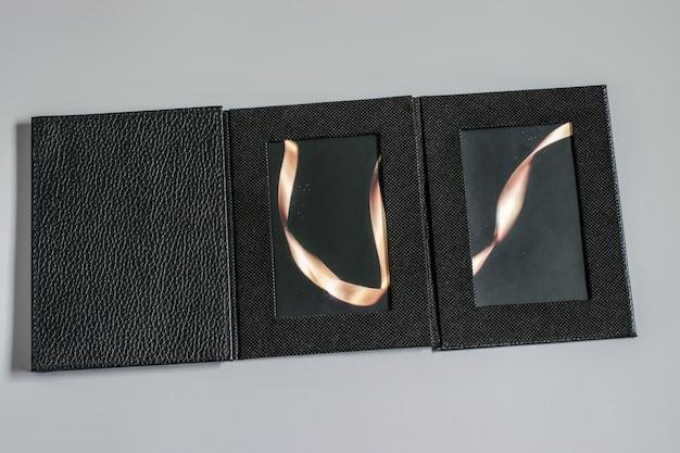 Schwarzes leeres fotoalbum-entwurfsmodell auf dem grauen hintergrund. schönes leeres modell mit platz für ihre zwecke: bilder, valentinstag, text und mehr.