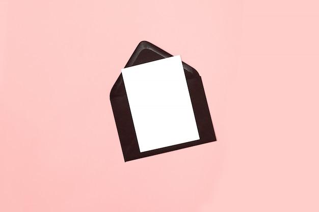 Schwarzes leeres umschlagmodell mit leerem buchstaben. flach liegen