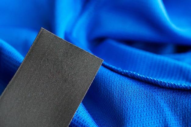 Schwarzes leeres wäschepflegeetikett auf blauem polyester