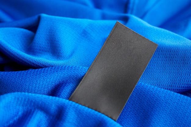 Schwarzes leeres wäschepflegeetikett auf blauem trikot