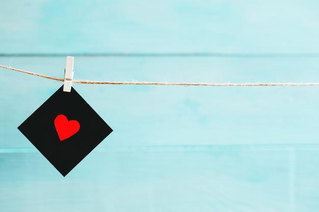 Schwarzes leerzeichen und rot mit ihrem inneren verbreiteten auf einer zeichenkette über blauem hintergrund. valentinstag hintergrund.