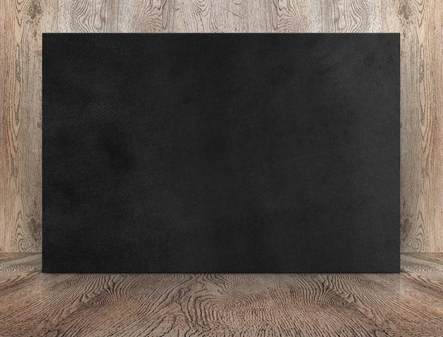 Schwarzes leinwandplakat des leeren banners, das an holzwand auf holzboden im perspektivischen raum lehnt