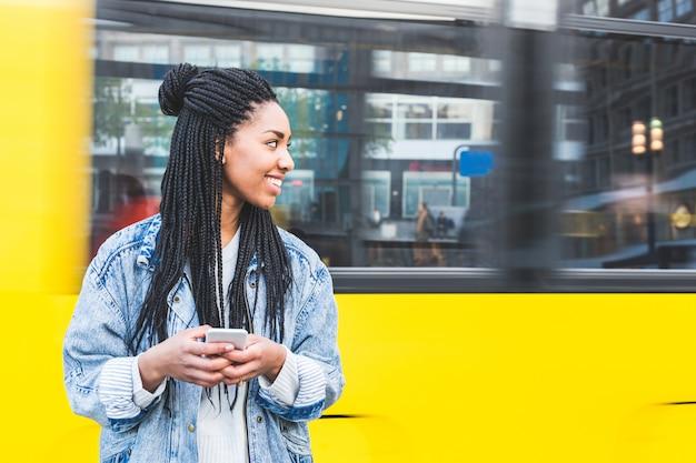 Schwarzes mädchen, das auf smartphone in berlin schreibt