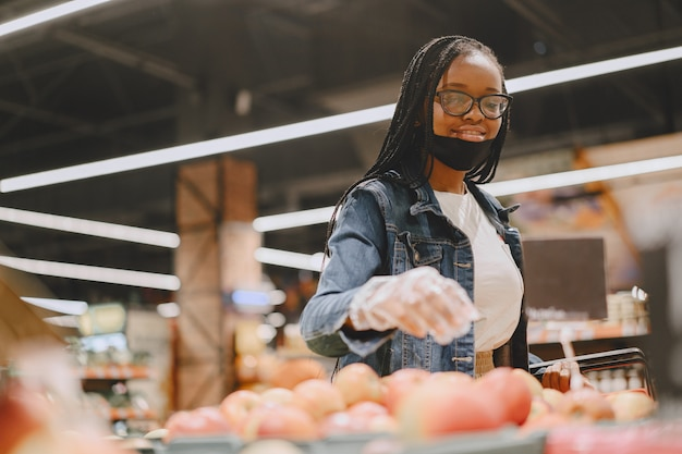 Schwarzes mädchen in einer maske kaufen ein essen