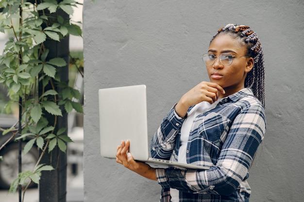 Schwarzes mädchen in einer sommerstadt mit laptop