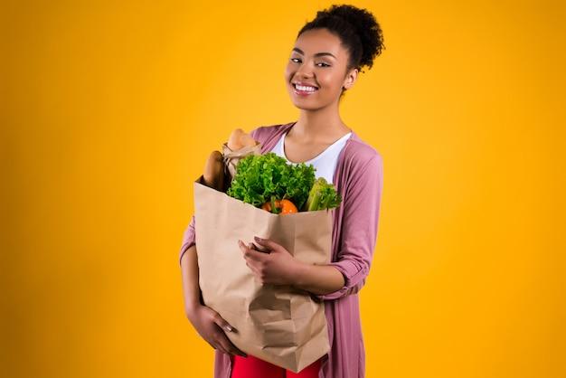 Schwarzes mädchen mit einem paket von produkten