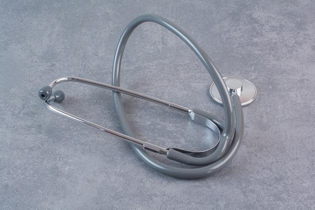 Schwarzes metallstethoskop auf marmortisch.