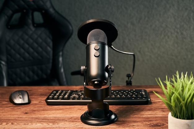Schwarzes mikrofon auf einem hausgemachten studio, das bereit ist, einen podcast zu streamen