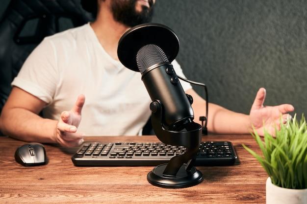 Schwarzes mikrofon in einer podcast-sitzung mit einem jungen mann in einem live-streaming
