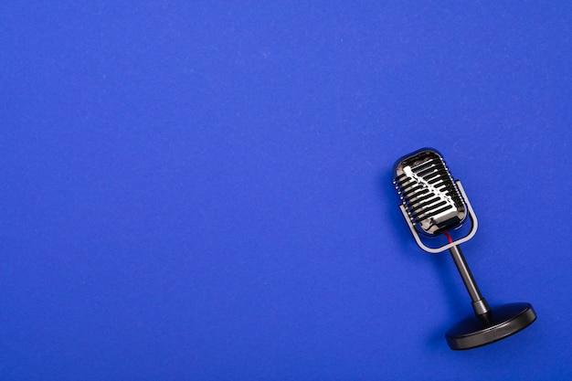 Schwarzes mikrofon lokalisiert auf blauem hintergrund