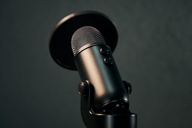 Schwarzes mikrofon mit popfiltermaske auf dunkelgrau