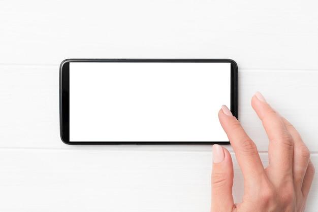 Schwarzes modernes smartphone mit weißem bildschirm in den händen auf weißem tischhintergrund