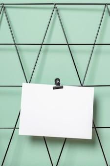 Schwarzes moodboard mit postkarten- oder erinnerungsmodell an einer grünen wand an einem freiberuflichen arbeitsplatz