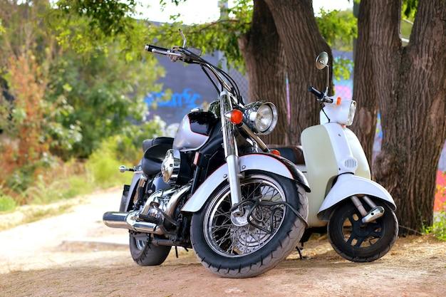 Schwarzes motorrad der weinlese, das nahe weißem motorrad in den strahlen des sonnenlichts steht. seitenansicht