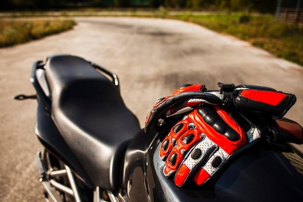 Schwarzes motorrad mit dem reiten von roten handschuhen