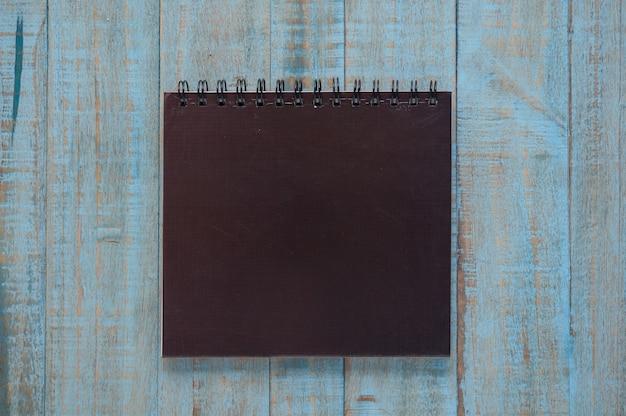 Schwarzes notizbuch auf blauem holz tisch