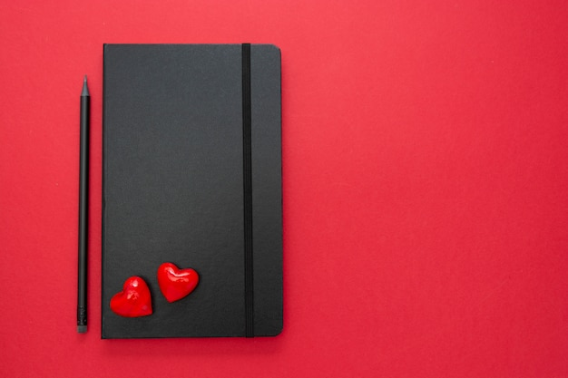 Schwarzes notizbuch auf rotem hintergrund mit zwei herzen. tischplatte für eine liebe, valentinstag nachricht.