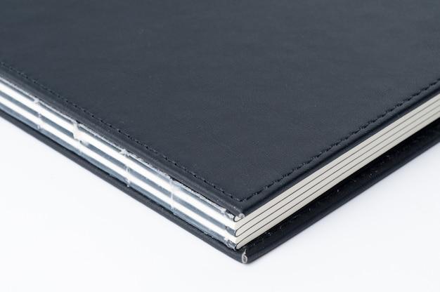 Schwarzes notizbuch auf weißem hintergrund.