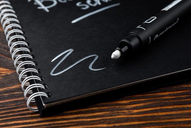 Schwarzes notizbuch mit text zurück zur schule auf dunklem hölzernem hintergrund.