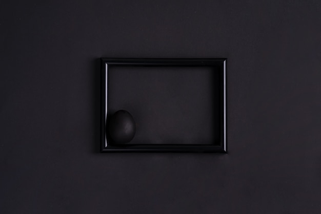 Schwarzes osterei durch pinsel in schwarz auf schwarzem fotorahmen