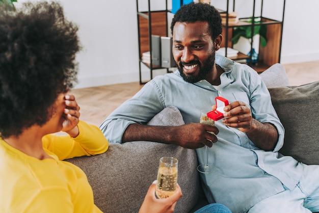 Schwarzes paar, das zu hause sekt trinkt, um zu feiern - fröhliche paarbindung und aperitif a
