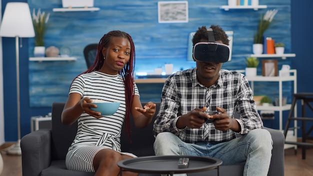 Schwarzes paar, das zu hause virtuelles spiel mit vr-brille spielt