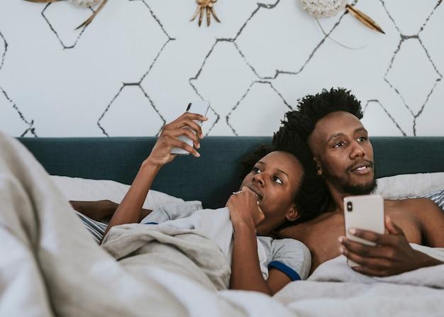 Schwarzes paar im bett mit einem smartphone