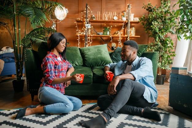 Schwarzes paar sitzt auf dem boden und trinkt kaffee gegen eine couch zu hause.