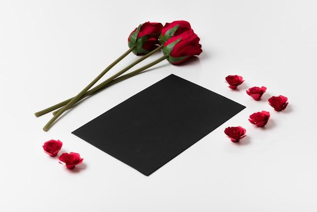 Schwarzes papier mit rosen auf dem tisch