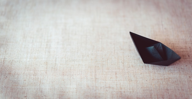 Schwarzes papierboot auf segeltuchbeschaffenheitshintergrund mit kopienraum