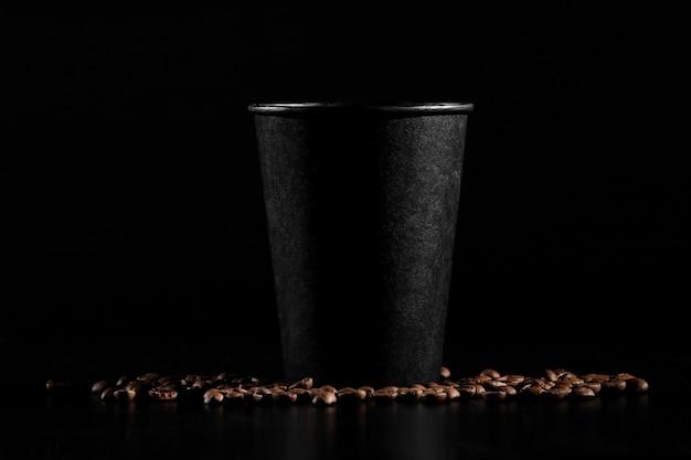 Schwarzes papierglas auf schwarzem hintergrund. kaffeebohnen auf einem dunklen hintergrund.