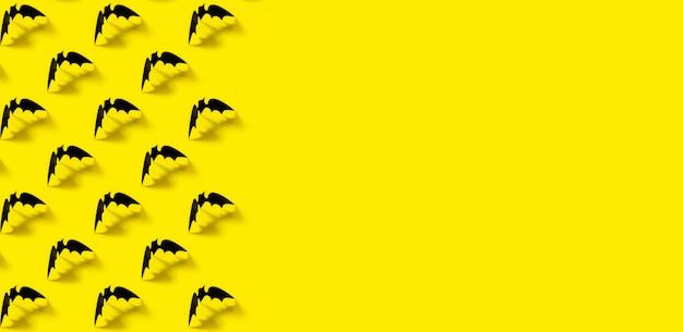 Schwarzes papierschlägermuster mit fallendem schatten auf gelb.
