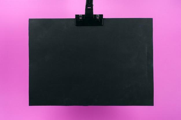 Schwarzes plakat auf rosa hintergrund.