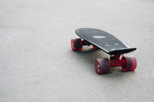 Schwarzes plastikskateboard mit roten rädern auf asphalt