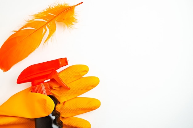 Schwarzes reinigungsspray in der hand im orangefarbenen handschuh und in der orangefarbenen feder auf weißem tisch