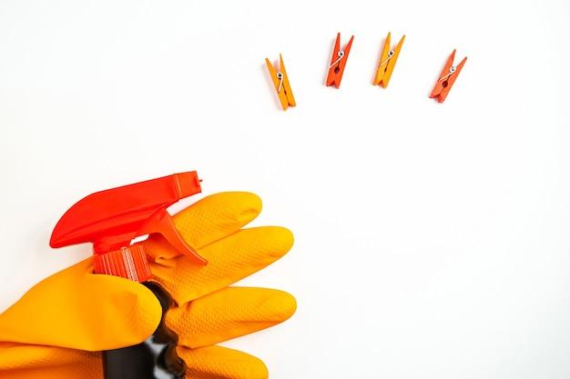 Schwarzes reinigungsspray in der hand in orange handschuh und wäscheklammern auf weißem tisch