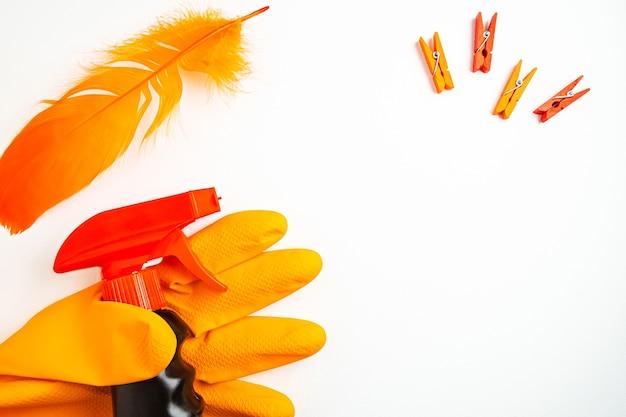 Schwarzes reinigungsspray in der hand in orange handschuh, wäscheklammern und orange feder auf weißem tisch